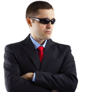 Young man in security guard pose with suit and shades