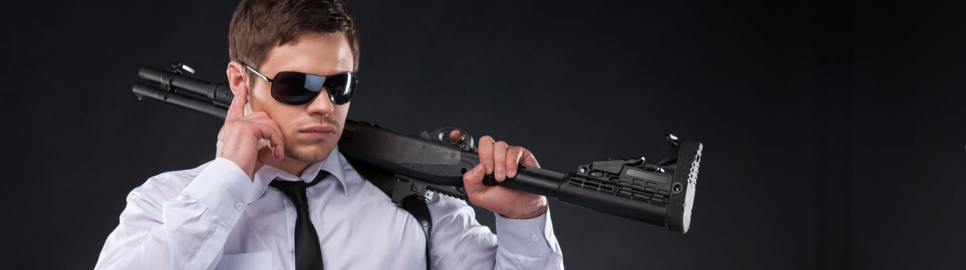 Confident young man in shirt and tie holding gun
